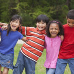 Diverse children standing in a row outdoors